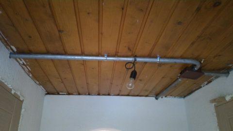На фото разводка проводов освещения по деревянному перекрытию выполнена в стальной трубе