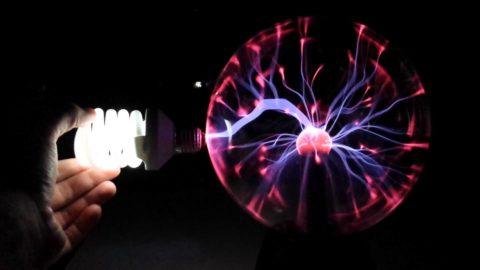 Переменный ток от плазменного шара заставляет светиться люминесцентную лампу